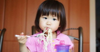 Young Girl Eating Noodles
