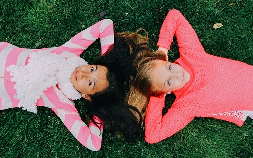 Two teens lying on the grass