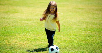 Girl kicking soccer ball on the grass