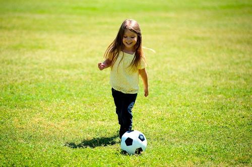 Girl kicking soccer ball on the grass
