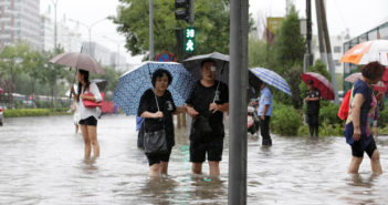 People stand on a flooded street during a heavy rainfall in Shilipu, Chaoyang Road, Beijing